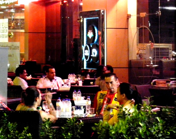 Men and women hang out at a cafe in Dubai. many cafes are open till 4am or through the night.