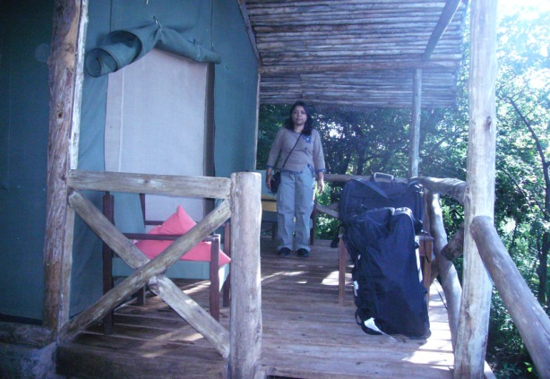 Chandrani in front of a cottage with a zipped door in Tanzania