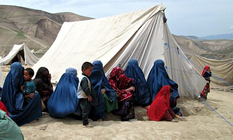 Women in blue burqas sitting next to make-shift shelters after the landslide claimed thousands of lives in Afghanistan